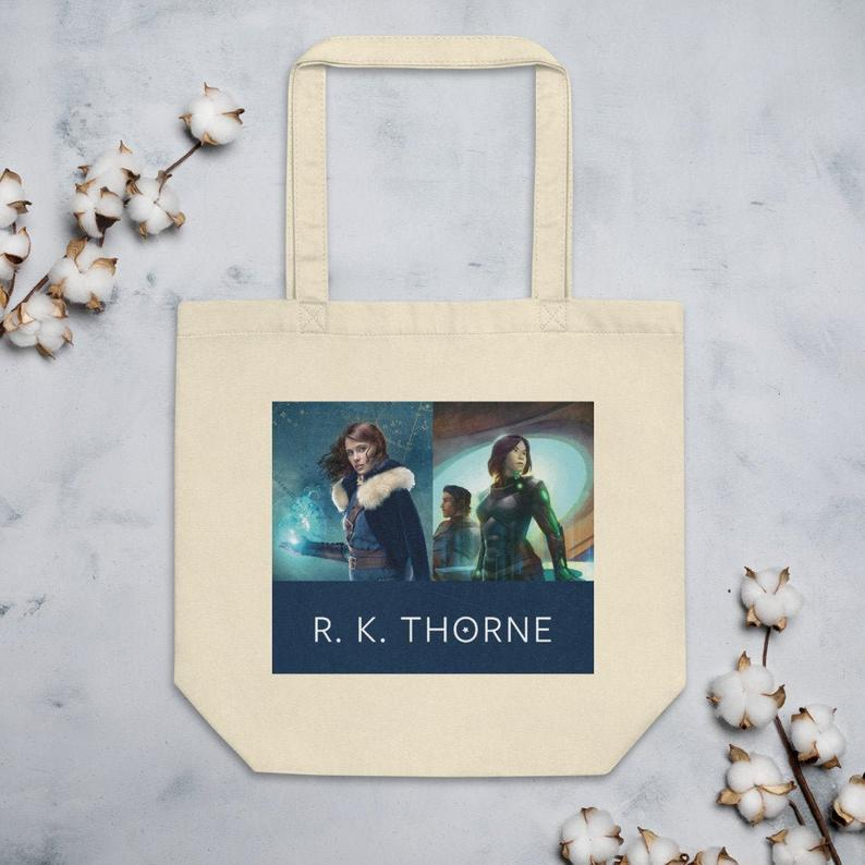 A beige eco tote bag with images from R.K. Thorne book covers featured on a gray background with some cotton plants