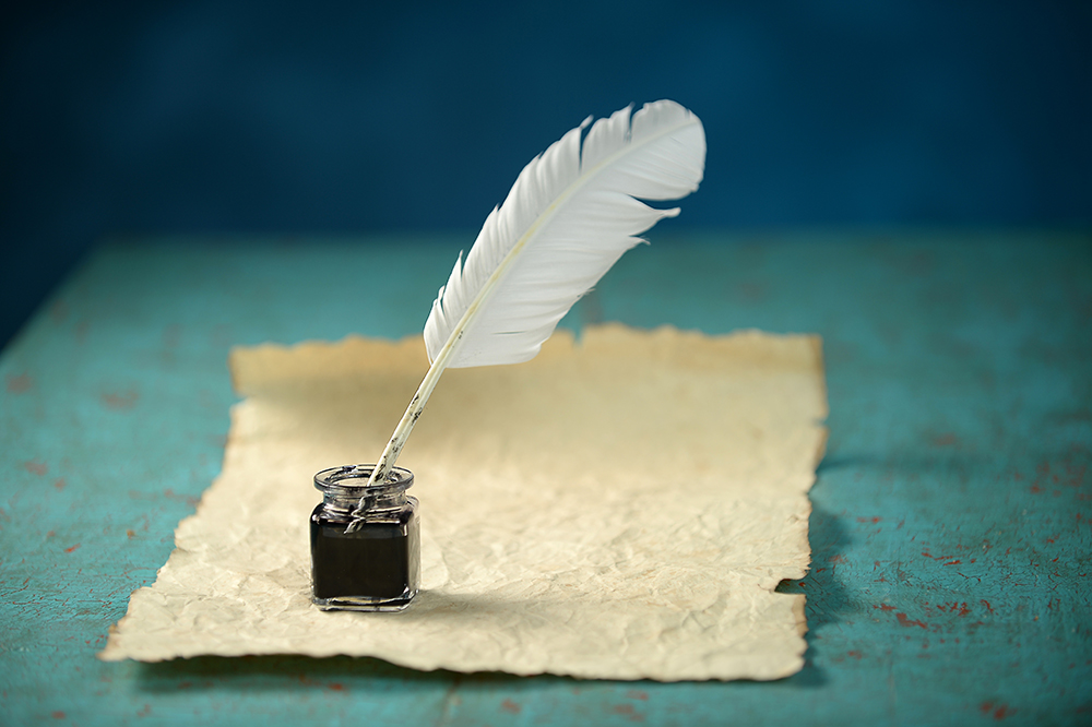 A bottle of ink and a quill set on a piece of parchment on a teal background.