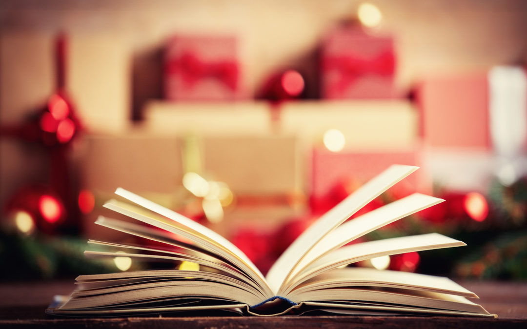 Open book and christmas gift and baubles on background